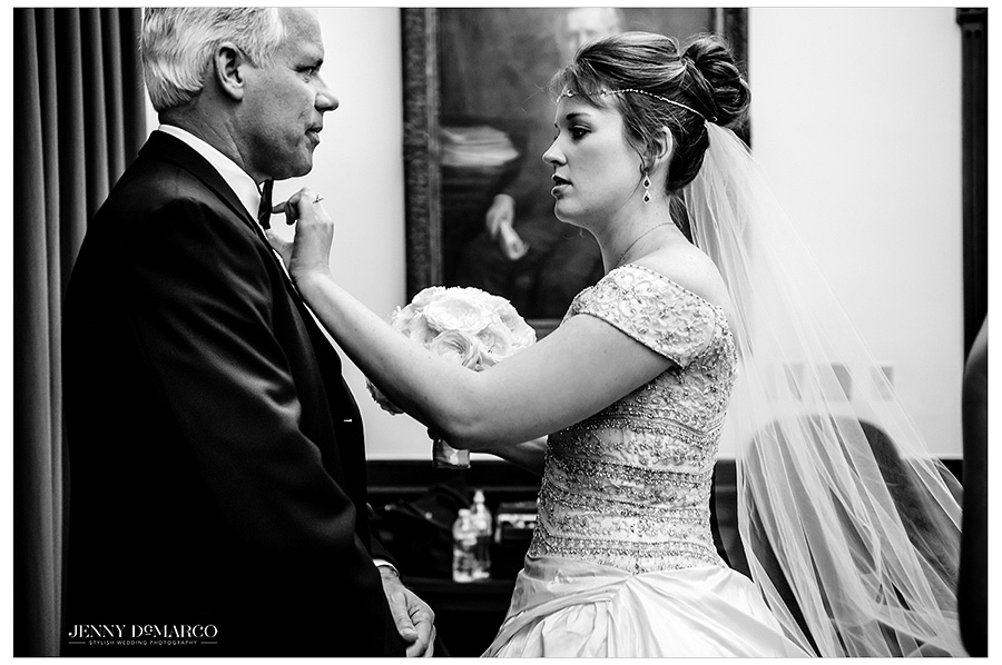 Bride Catherine adjusts her dad's tie as he looks lovingly and proudly at his daughter.