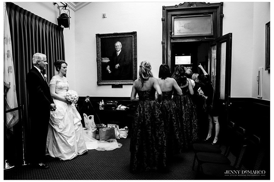 A black and white image of the bride and her father wait in the conference room of the Senate as the bridesmaids file out.