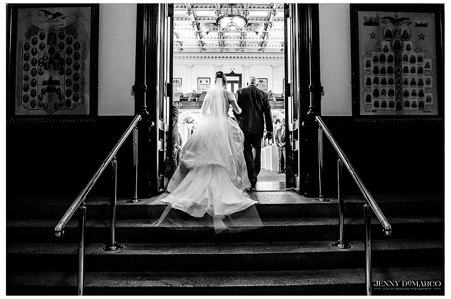 A black and white image of the bride and the father of the bride entering the ceremony. The image is from behind as to show off the veil and train of the bride.