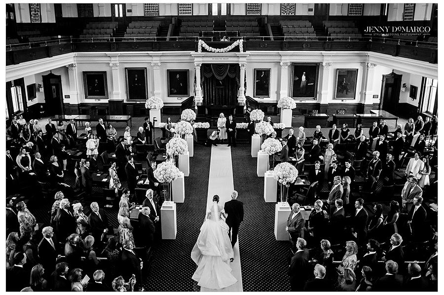 Black and white overhead shot emphasizing the wedding guests, the bride and her father, the groom and minister, and the overall beauty of the Texas Senate chambers.