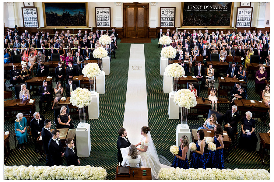 Shot from behind the altar emphasizing the wonderful peonies arrangements and the couple holding hands. Wedding guests admire the bride and groom from the senate tables.