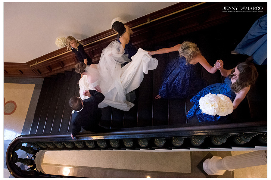 Cousins of the bride hold the dress's train as the newleyweds make their way down the stairs to go to the reception.