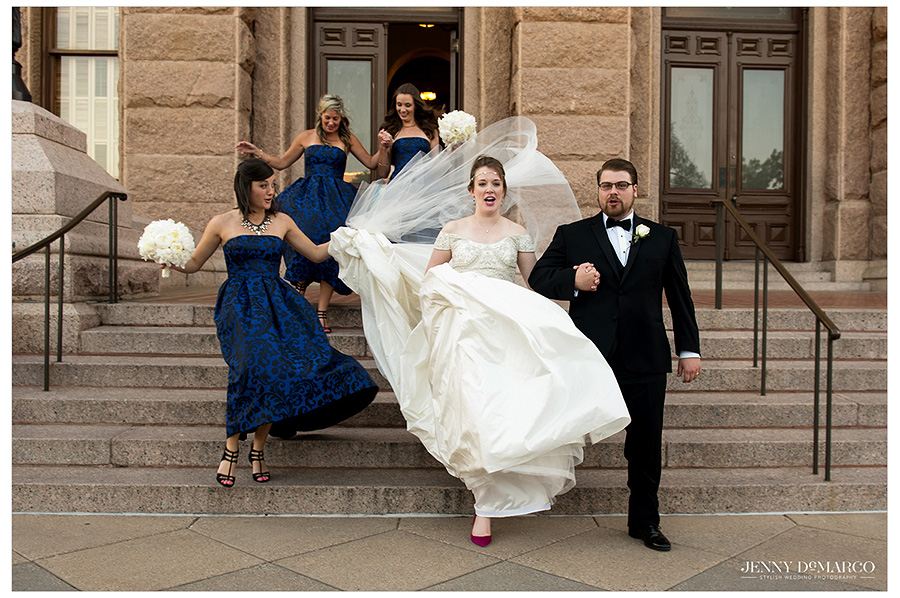 Newlyweds make their way down the stairs of the Texas State Capitol followed by the bridesmaids. Also emphasized in this image is the fuchsia shoe of the bride, giving her a pop of color in her look.