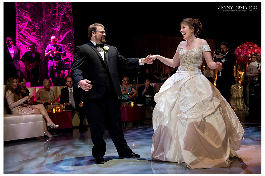 Bride and groom laugh heartily on the dance floor as they share their first dance together as a married couple.