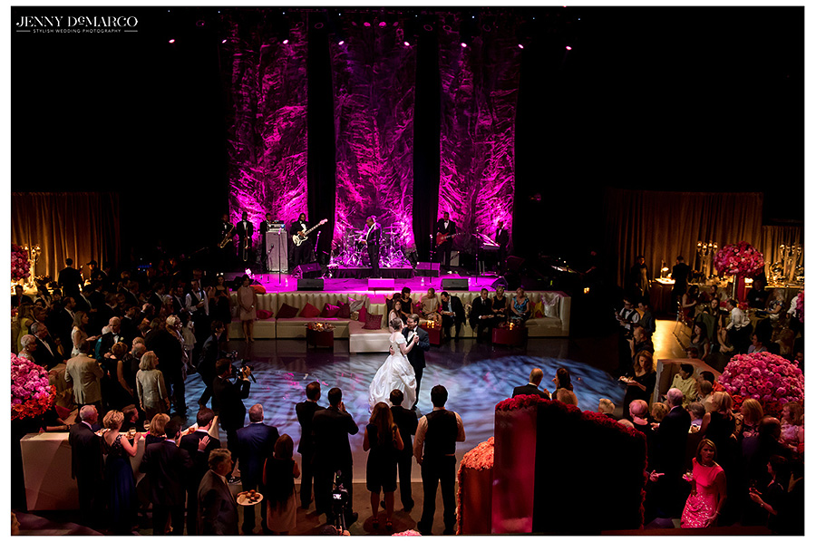 The bride and groom share their first dance in front of adoring guests backlit by the vivid three paneled fuchsia stage.