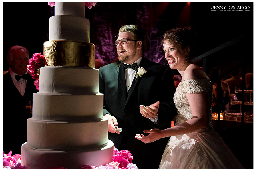 Married couple Catherine and Preston cut their seven tiered cake and laugh at the witty banter of their onlooking guests. The multi tiered cake has one single gold layer as an accent.