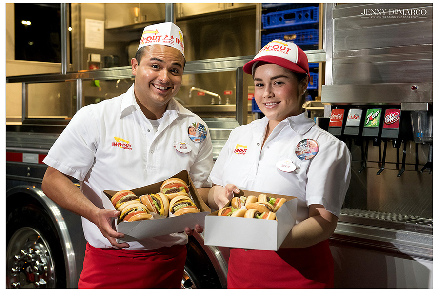Two In-N-Out workers hold boxes of the legendary California burgers for guests to enjoy and take home as the reception draws to a close.
