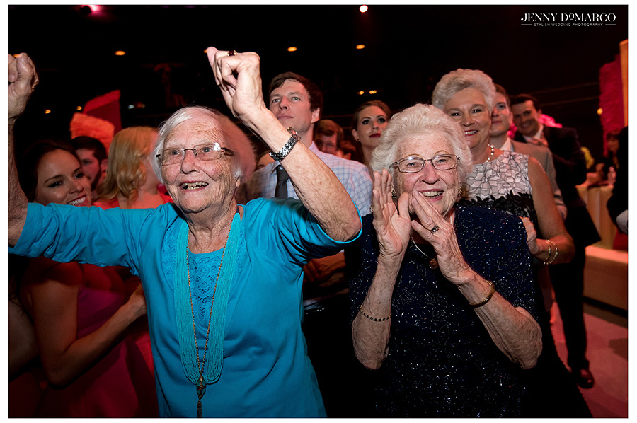 Two grandmothers at the party clap and sing along to the rhythmic beats of the soul band.