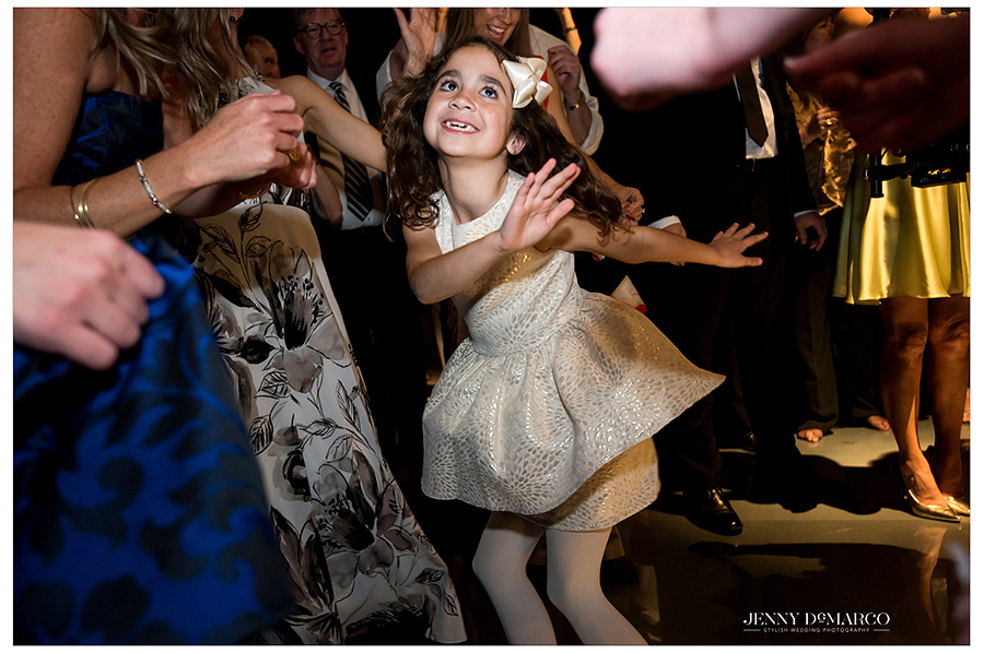 A cute little girl wearing pigtails and bows does the twist and shout at the wedding reception.