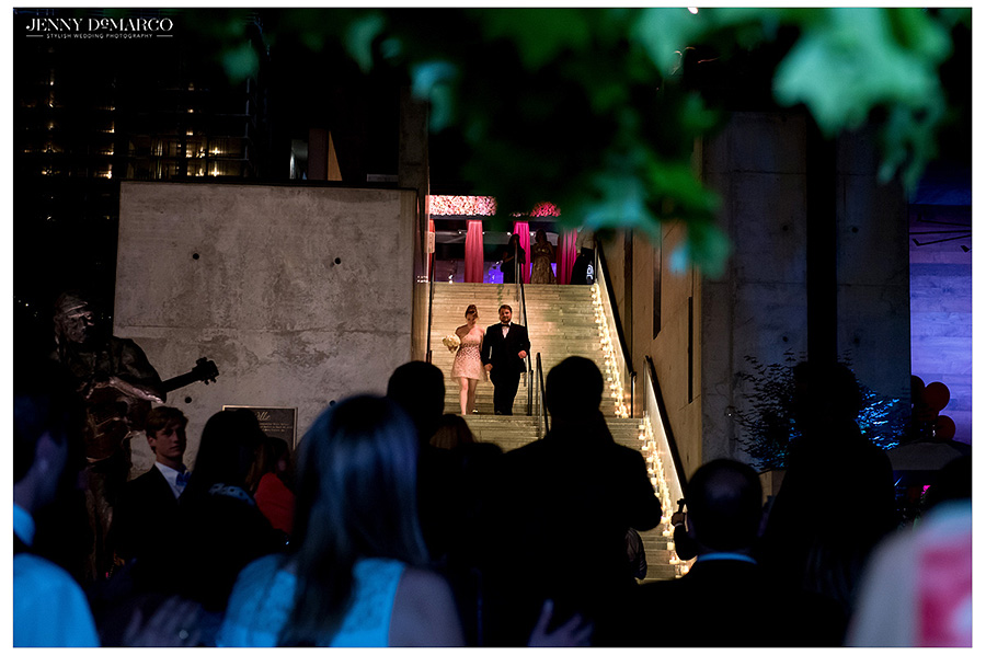 Bride and from walk down the illuminated staircase of the ACL Moody Theater as family and friends cheer from below.