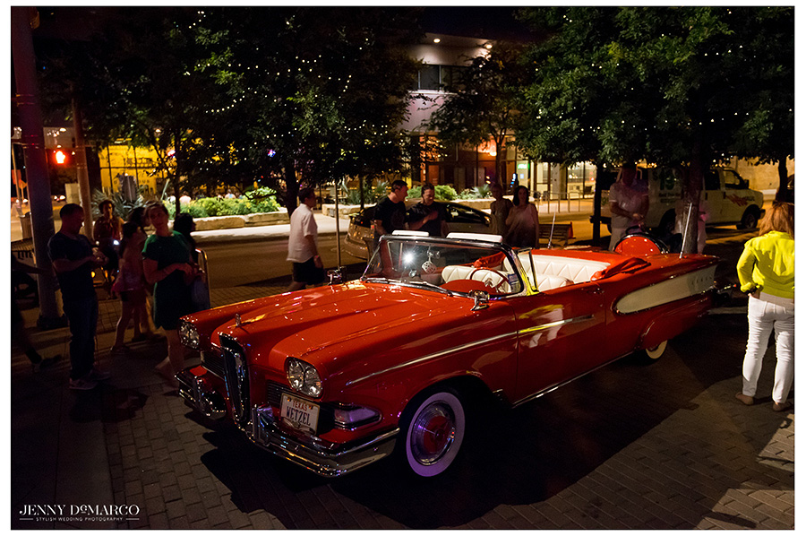 The bride and groom make their way towards the vintage red and white convertible that will take them to their hotel.