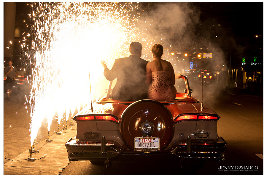 Mr. and Mrs. Watson sit on the back of the vintage red and white convertible as they make their way through the tunnel of sparklers that is their exit.