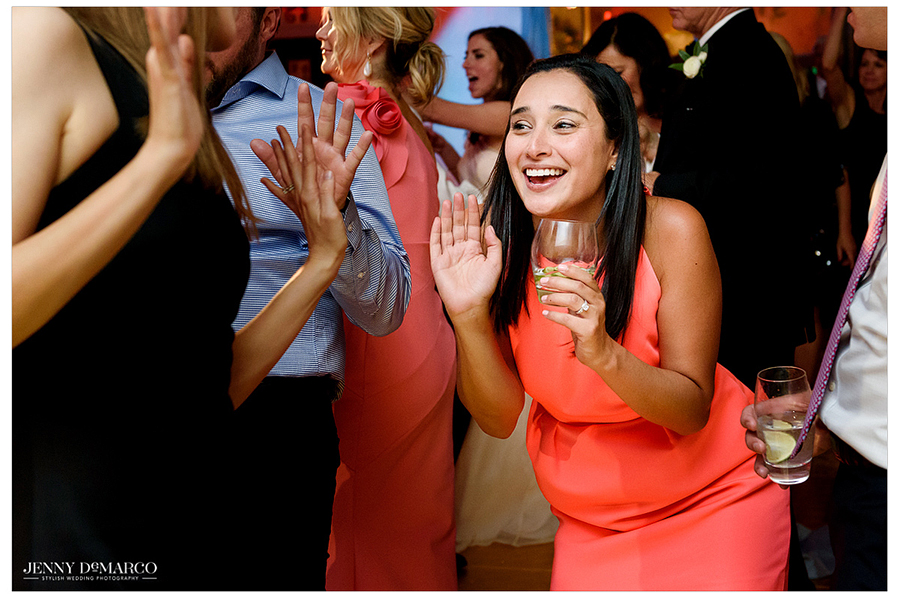 Girl in orange dress smiles on the dance floor