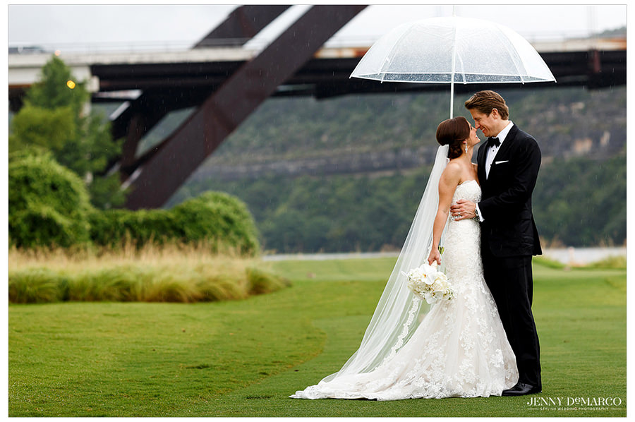 The bride and groom standing under the umbrella on the Austin Country club golf course with the Austin bridge in the background.