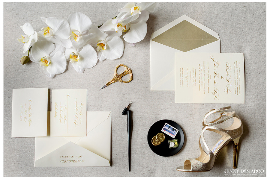 A detail photo of the bride's wedding day Jimmy Choo shoes, wedding invitation, and other accessories.