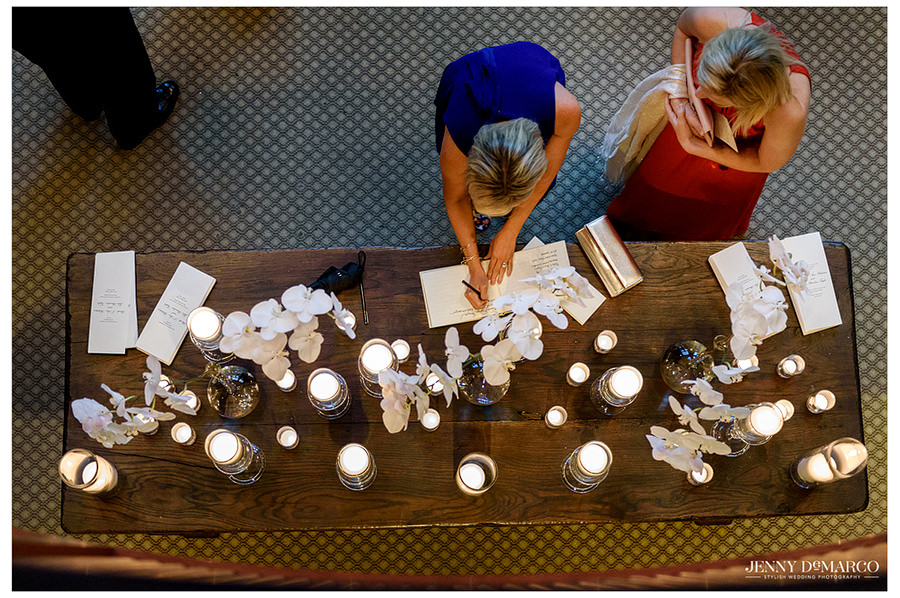 Friends and family sign the guest book on a table with candles and flowers before entering the church.