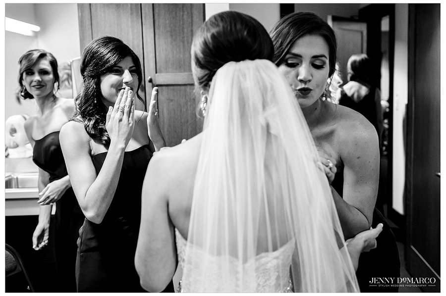 The bridesmaids have their first look at the bride in her dress and veil and give her hugs and love before the wedding.