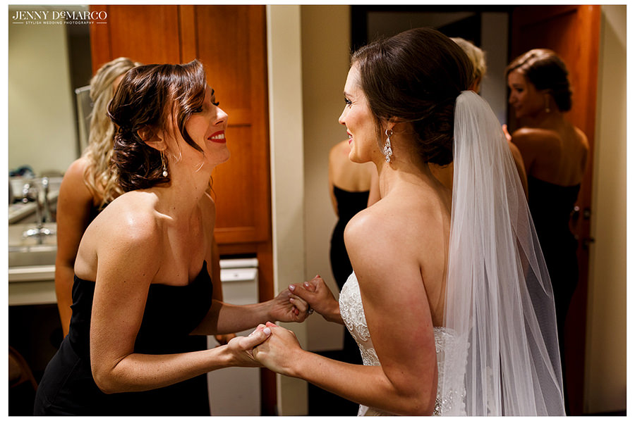 The bride and one of her bridesmaids share a moment of joy and love while holding hands before entering the church.