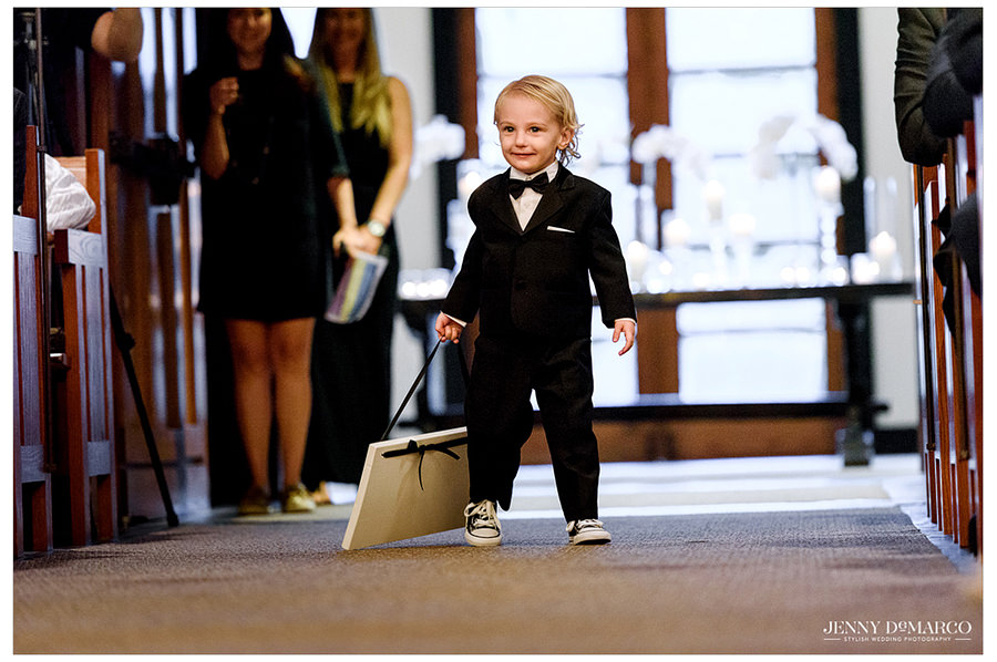 The ring bearer heads down the aisle in a small tux and converse while holding a sign to welcome the bridesmaids and the bride.