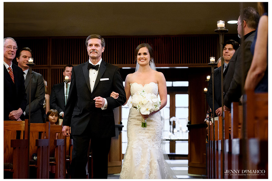 The bride and her father walk down the aisle as the guests all rise to watch.
