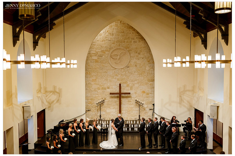 A view of the bride and groom holding hands during the ceremony surrounded by the bridesmaids and groomsmen. The Cross, candles, and musicians are shown in the background.