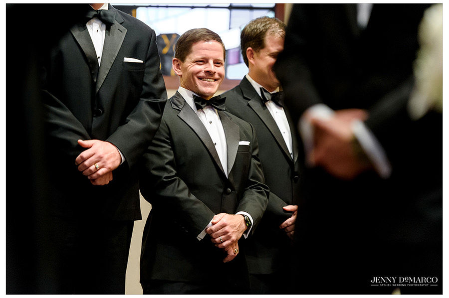 A groomsmen smiles at the bride and groom during the wedding.