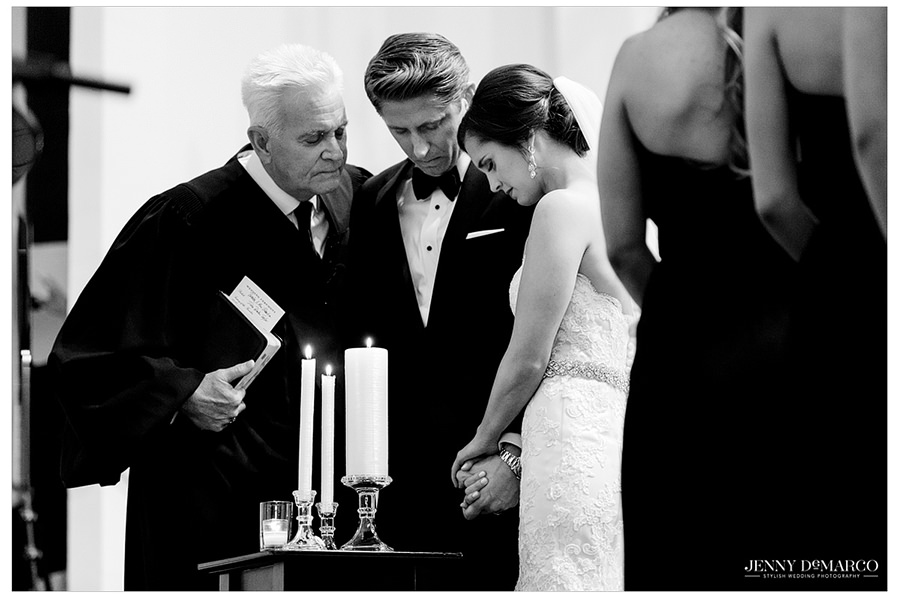 The bride, groom, and minister share a moment while holding hands and closing their eyes in prayer over candles after lighting their unity candle.