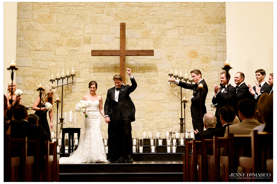 The groom holds his fist in the air with joy and excitement after the wedding as him and the bride walk down from the alter and down the aisle. The guests cheer and clap.