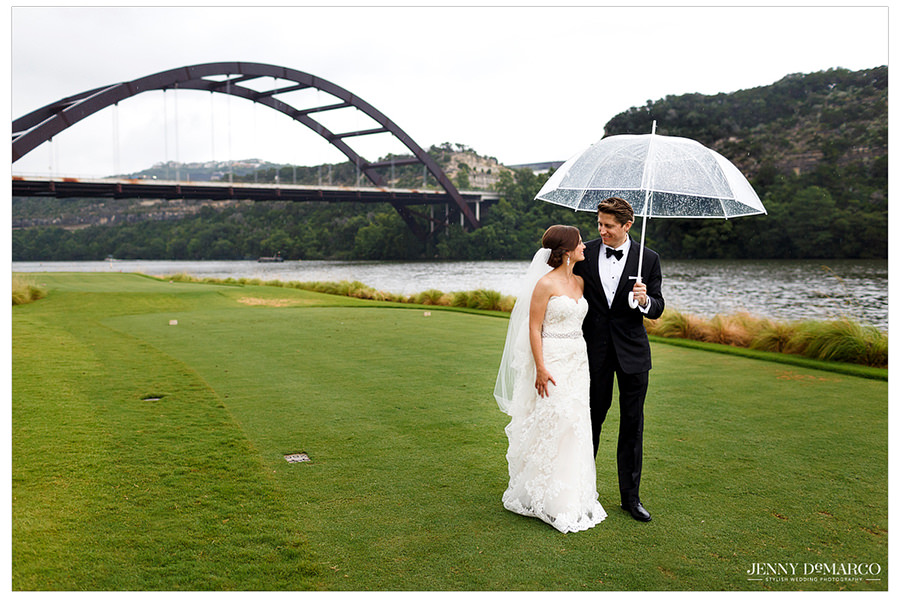 The bride and groom standing under the umbrella and looking into each other's eyes on the Austin Country club golf course with the Austin bridge in the background.