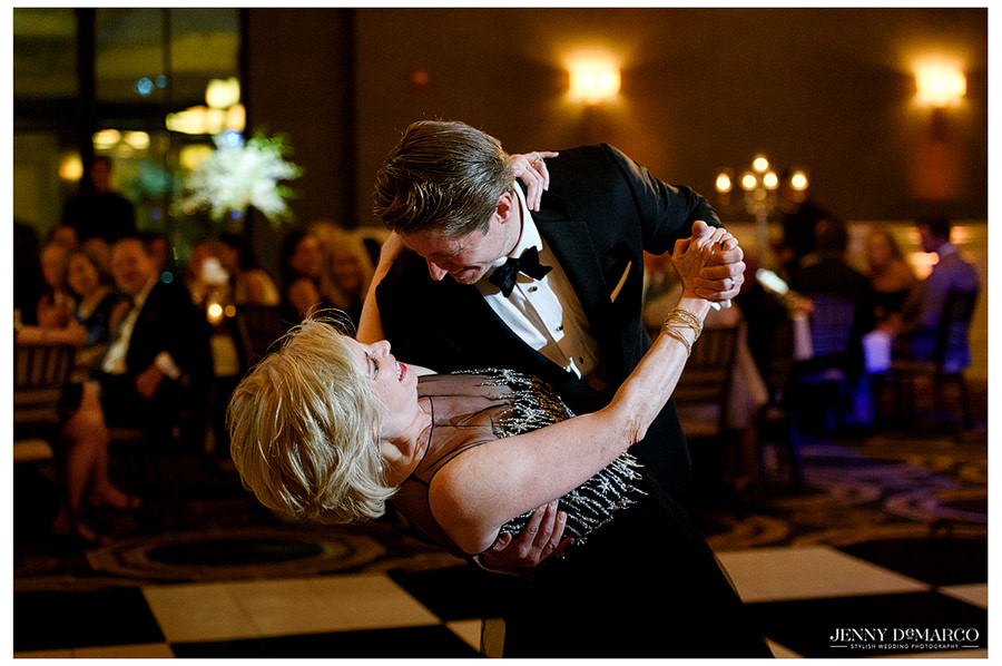 The groom dips his mother during their first dance as guests gather to watch.