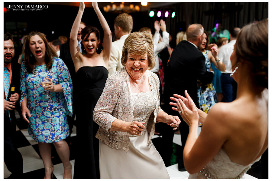 Guests clap and dance along with the bride on the dance floor of the Austin Country Club.