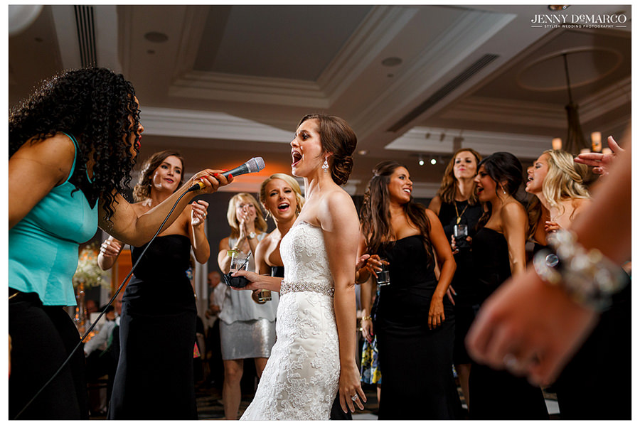 The lead singer of the band points the microphone to the bride to let her sing along with their song while her bridesmaids sing and dance along behind her.