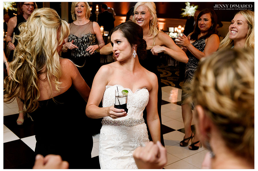 The bride and one her her bridesmaids look at each other and dance together on the dance floor as her friends laugh.