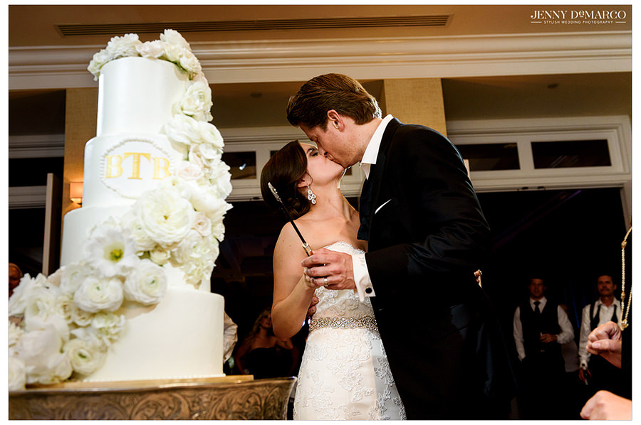 The bride and groom kiss beside their wedding cake which is decorated with flowers and a custom monogram.