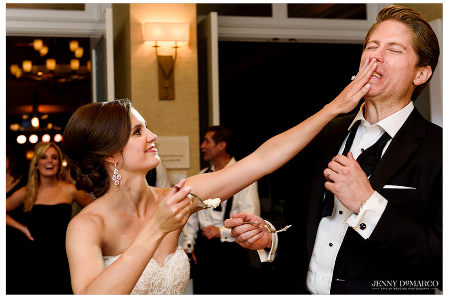 The bride playfully shoves cake in the grooms mouth after taking their first bite.