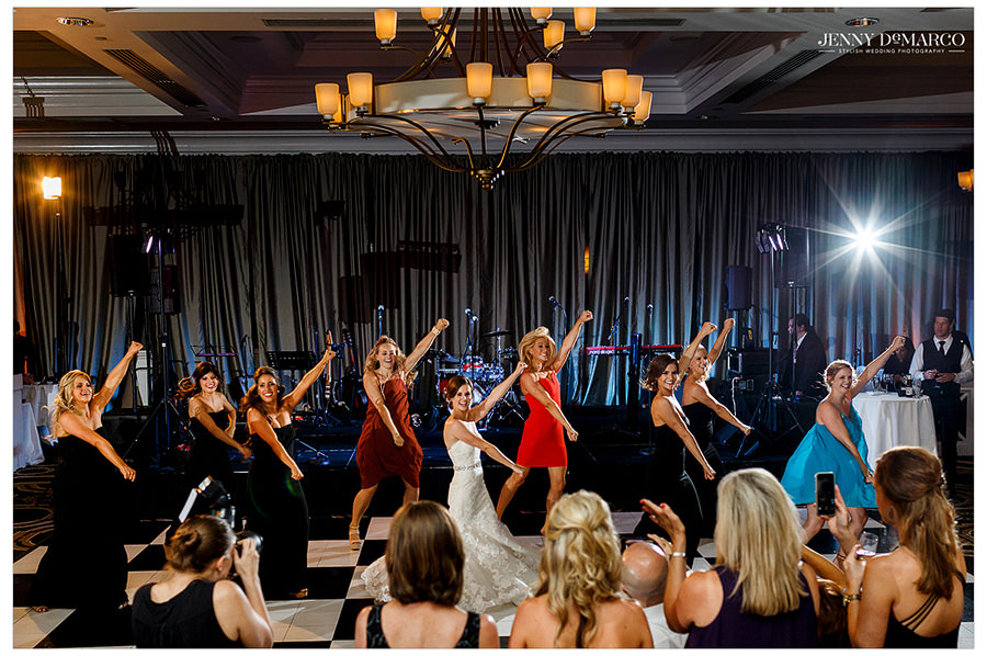 Friends and family gather to watch the bride and her Pom squad friends perform a dance routine on the dance floor.