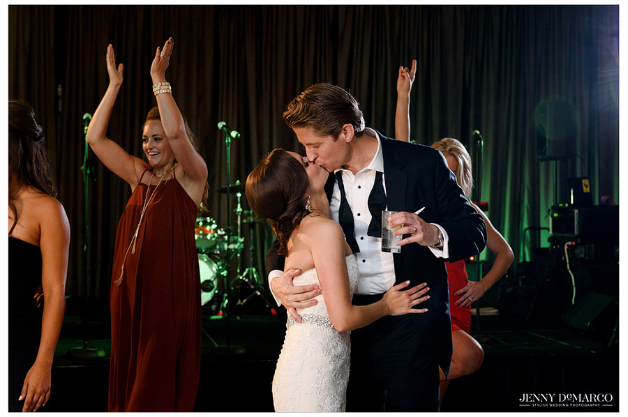 The bride and groom share a hug and kiss as guests dance and clap around them.