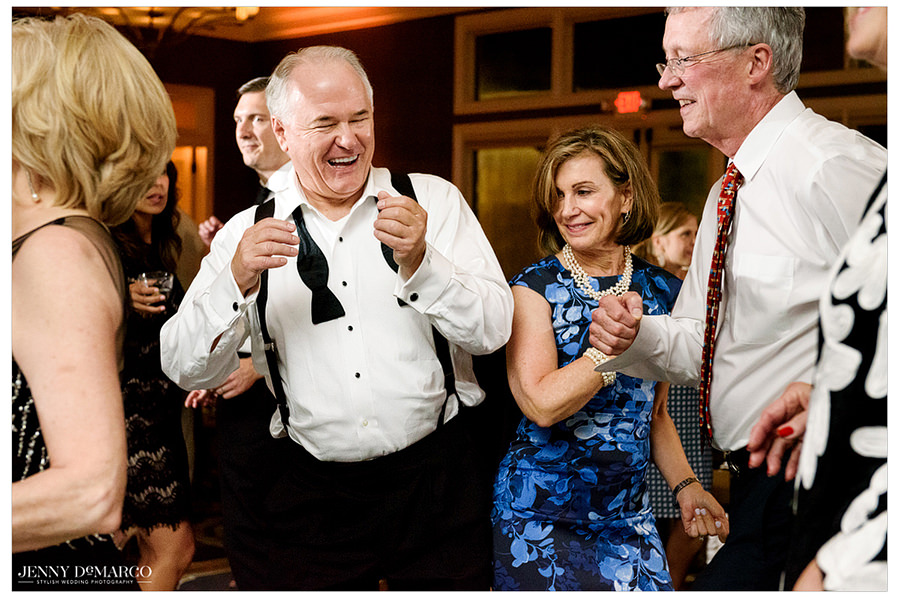 Two guests dance, laugh, and clap together on the dance floor.