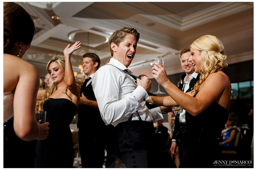 The groom does a funny dance move and other guests join and laugh.