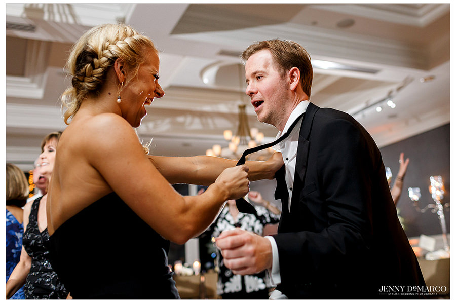 A bridesmaid pulls the tie of one of the groomsmen as they dance together.