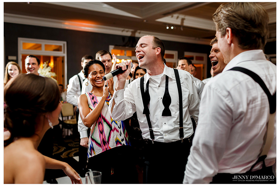 A groomsman sings loudly into the microphone as laughing guests surround him.