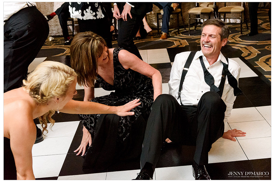 The parents of the bride sit and dance on the floor of the ballroom and laugh together.