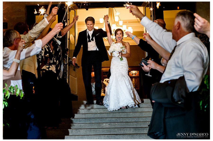 The bride and groom hold hands in the air while they make their exit down the stairs as guests hold sparklers and watch.