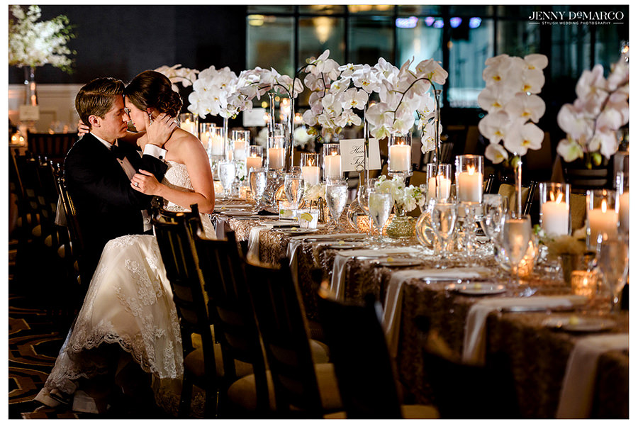 The bride and groom sit with each other at the head table of the ballroom.