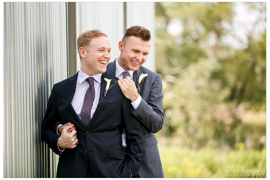 Grooms hold hands and hug during first look.