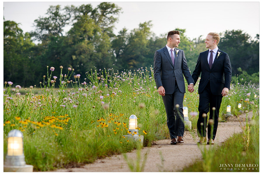 Portrait of grooms walking through a field in Hill Country.