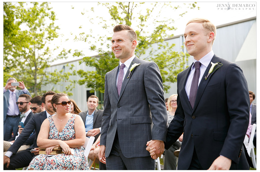 Grooms holding hands while walking down the aisle.