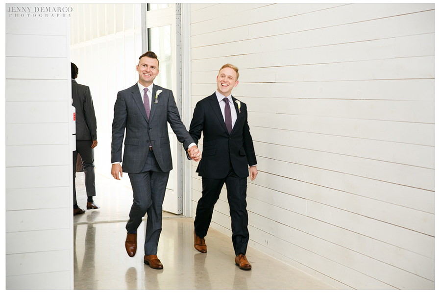 The grooms enter the wedding reception, hand in hand, for the first time as a married couple.
