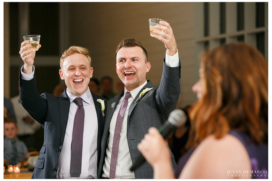 The grooms raise a glass during a friend's speech.