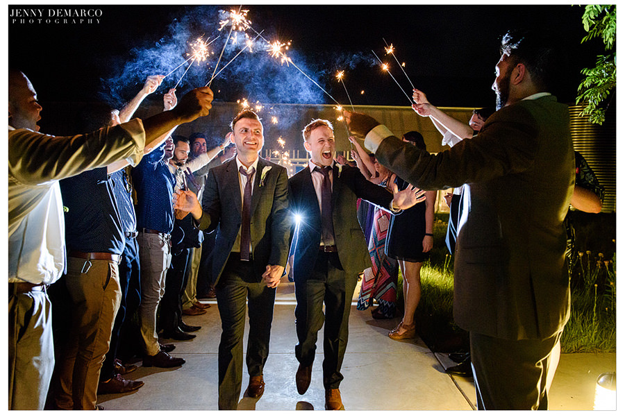 Grooms exit surrounded by friends and sparklers after a night of dancing.